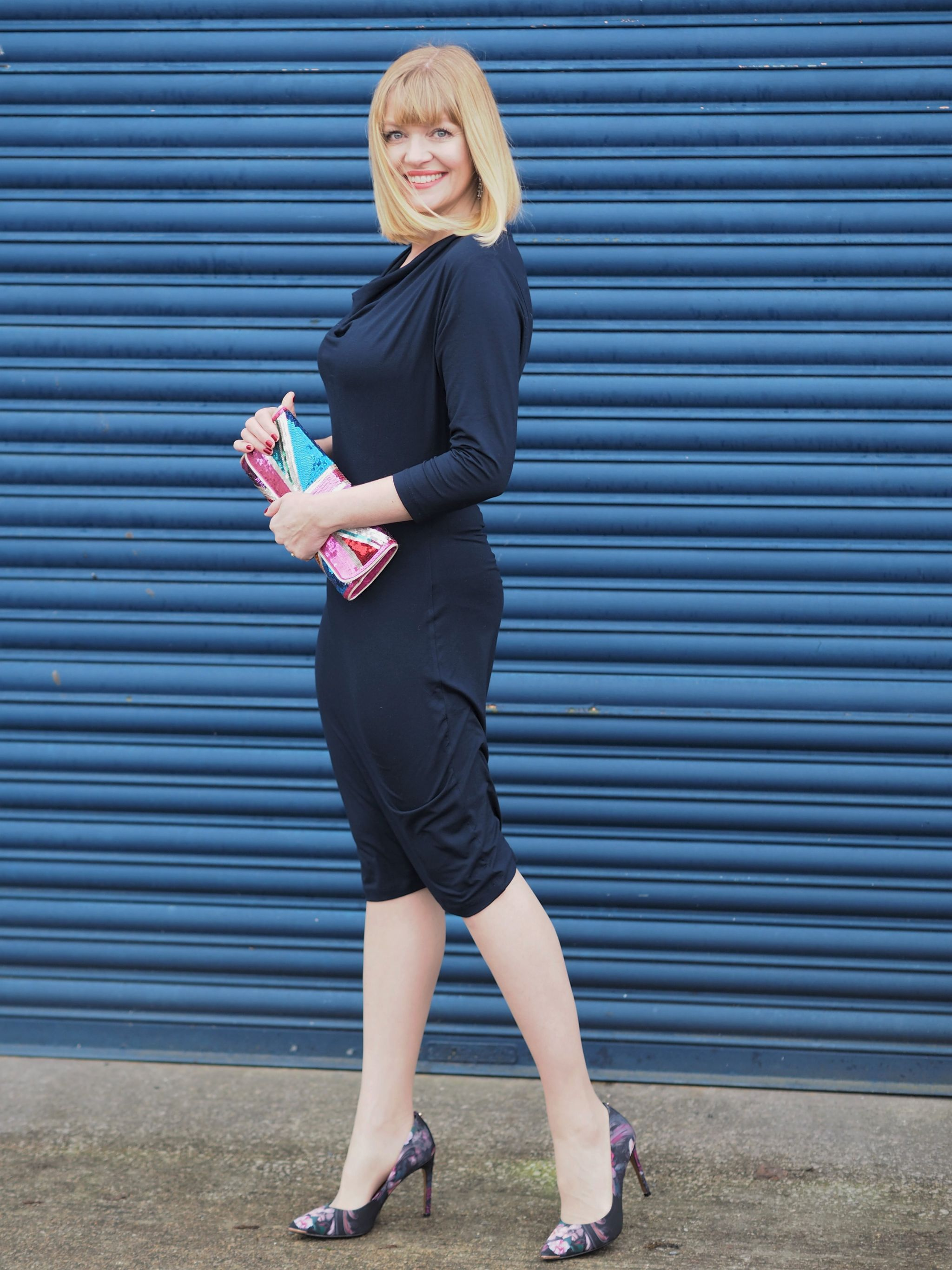 Over 40 blogger Lizzy wears navy cowl neck dress and floral court shoes