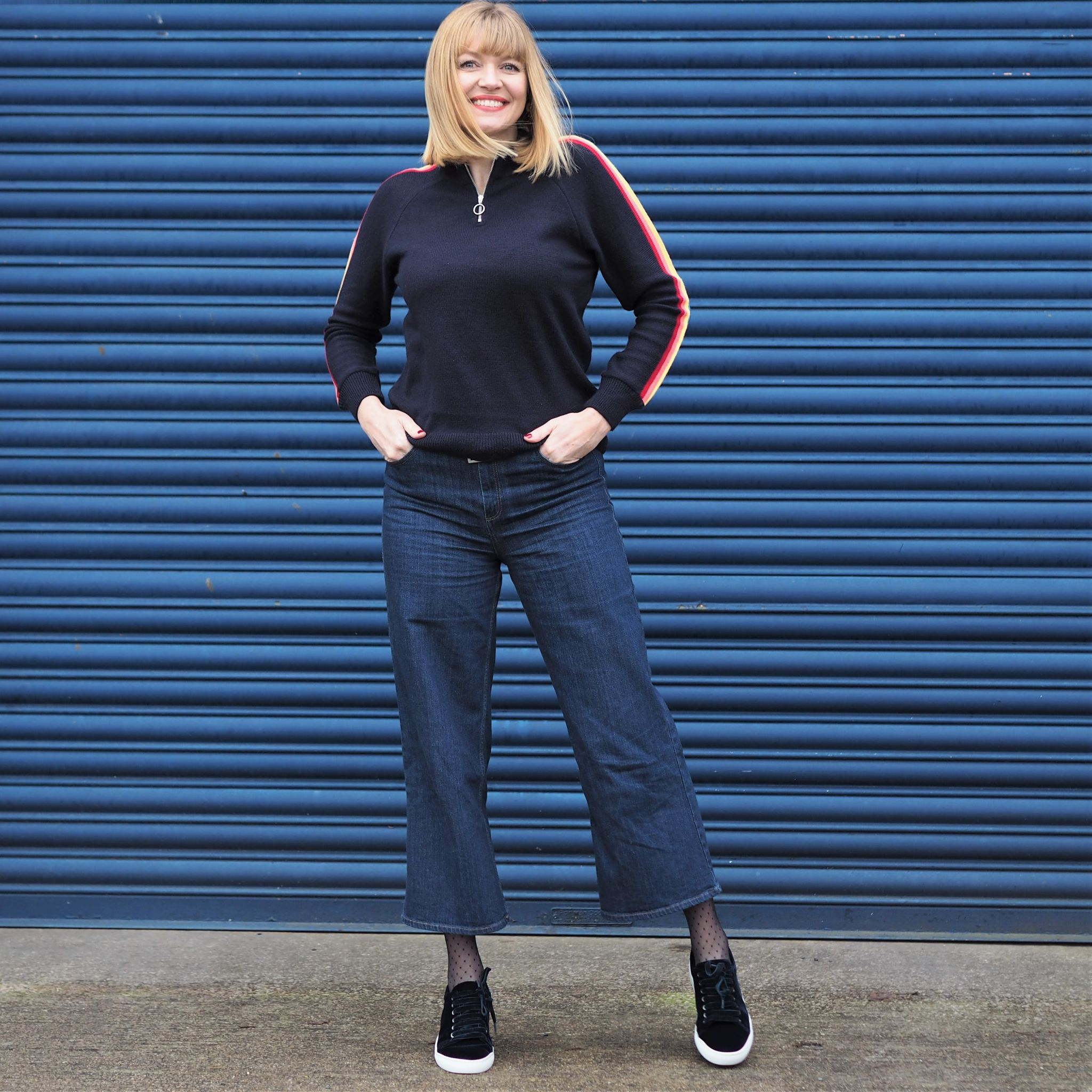 Forty plus blogger what Lizzy Loves wears rainbow sleeve sweater wuth wideleg jeans and velvet pumps