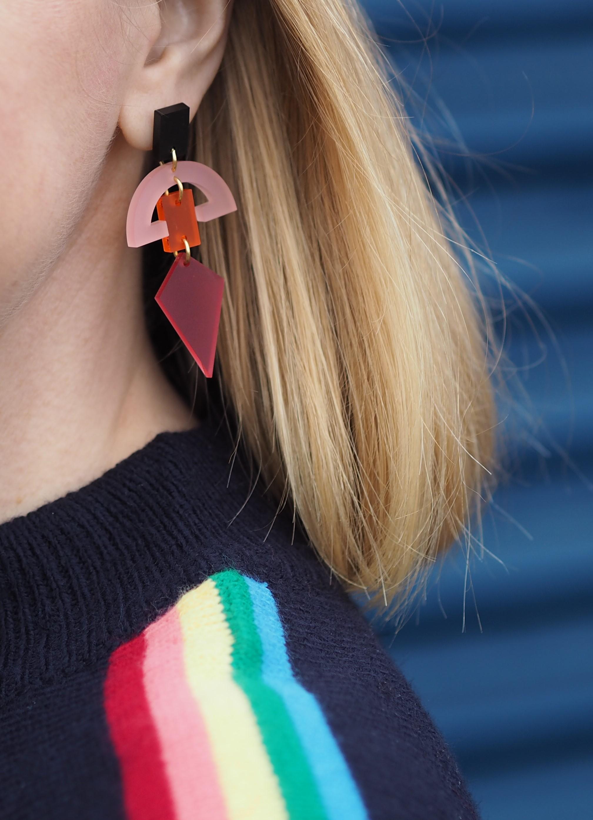 Pink half moon earrings worn with rainbow-stripe sleeve sweater