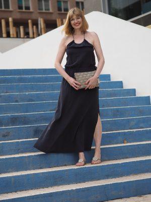 Navy silk halterneck dress and navy raffia clutch bag